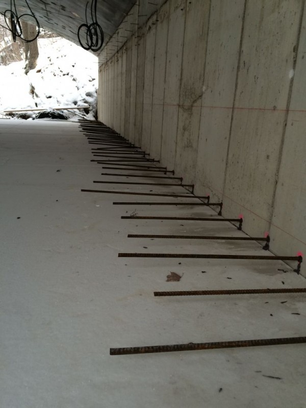 Rebar epoxied into the wall at the center of the slab.