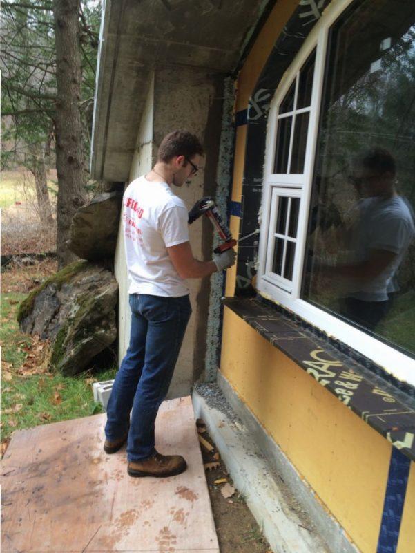 Jude finishing the spray foam around the windows.